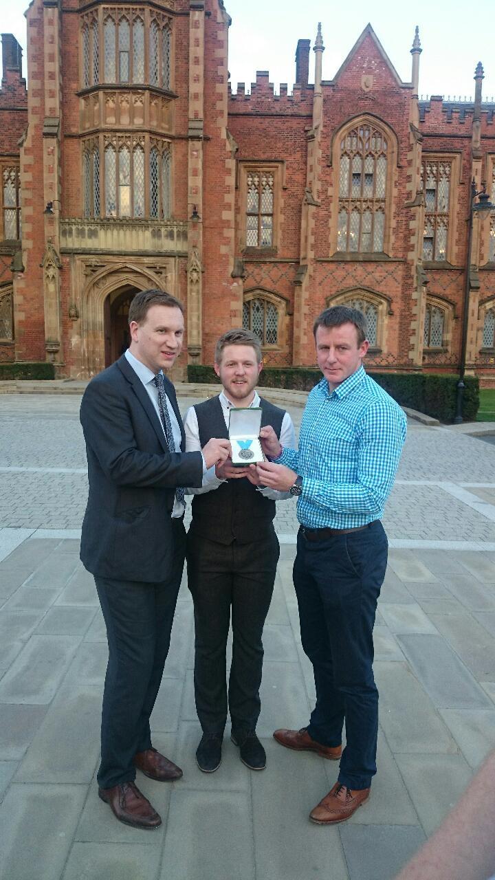 Michael Monan receives the Cormac McAnallen medal from Donal McAnallen  and alumni Justin McNulty